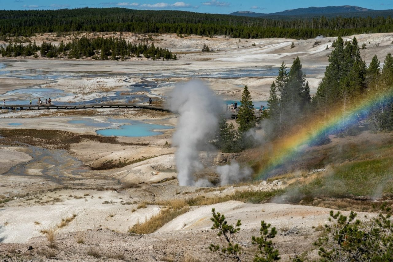 View of Norris Basin from the trailhead with a rainbow formed due to the mist formed by the geyser eruption
