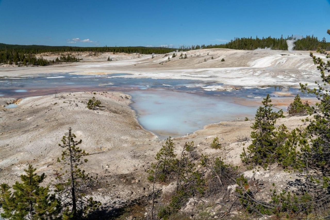 Turquoise blue waters of geyser in Norris Basin